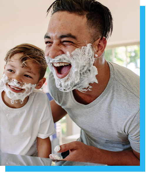 Dad and son looking in mirror laughing with shaving cream on face. Drainbo's all natural drain cleaner